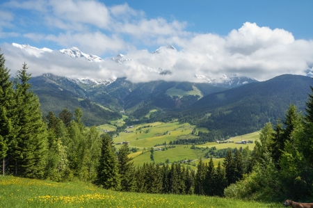 Scenery view from the mountain to the valley in Austrian Maria Alm with green grass, blue sky and snow