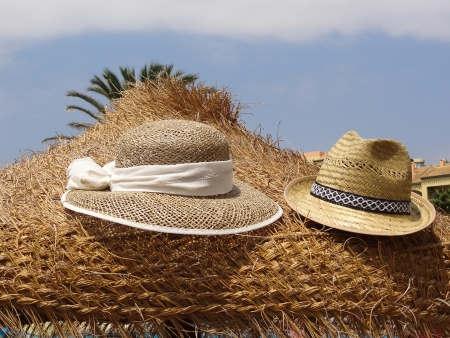 Womens and mens straw hats on a beach umbrella