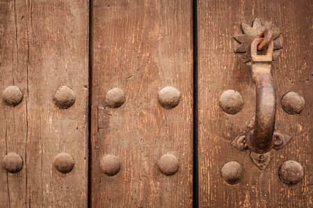 Fancy metal latch on an old wooden door