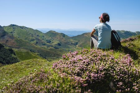 She is enjoying a magnificent high mountain landscape view surrounded by beautiful wildflowers at Alto Valle del Miera, Cantabria, Spain