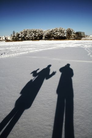 Cold solar winter day. The photographer and its girl-friend photograph the shades on pure snow. Stock Photo - 5748883