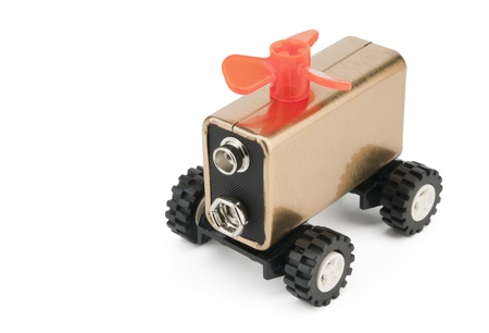 Gold battery on toy wheels macro isolated on white. Electric car concept