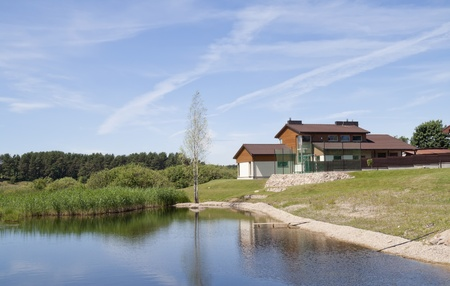 Rural houses are situated on the bank of the lake. A summer landscape photo