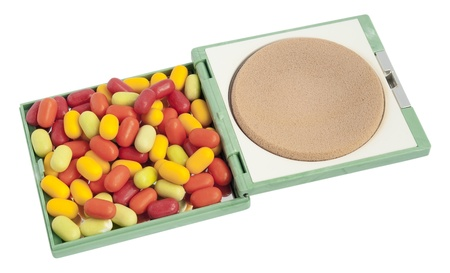 Multi-coloured tablets  pills  lie in a female powder box. Isolated with patch
