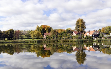 My small European village on lake  bank, reflections in water and cloudly October  autumn day Stock Photo - 10971602