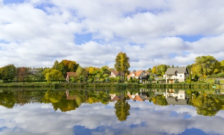 Dream European village on river bank, reflections in water and  solar autumn day Stock Photo - 12995696