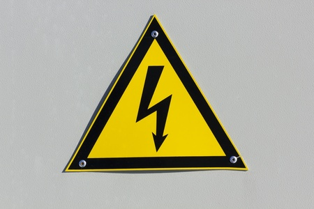 voltage gray: The International Standard sign Caution -High Voltage! on the wall of an industrial transformer background. Summy day Stock Photo
