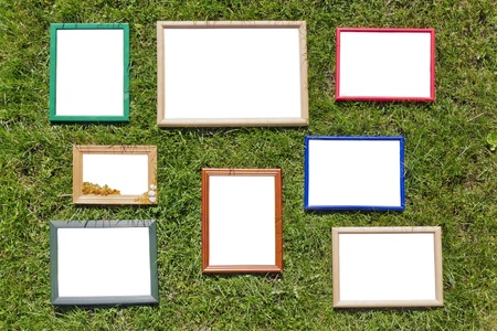 In the spring green lawn lie empty wooden picture frames. Contains patches. Outdoor image, sunny day