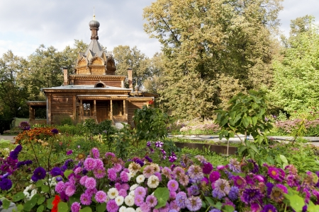 greem: Old wooden Russian Orthodox church in the woods of autumn flowers and trees landscape. Selective focus