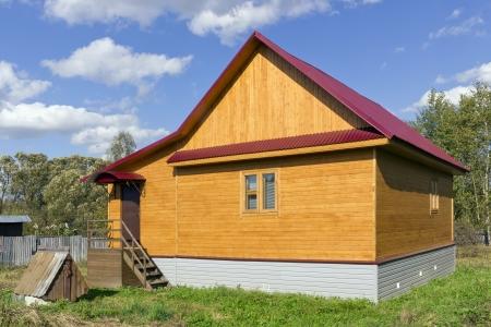 Casa rural de madera r�stica est� hecha a mano. Las paredes de tablas de pino tratada l�quido protector amarillo. Soleado d�a de septiembre Foto de archivo - 15950778