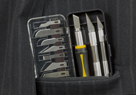 scalpels: Toys of young surgeon Jack concept. New scalpels in a pocket of a mans jacket. Stock Photo