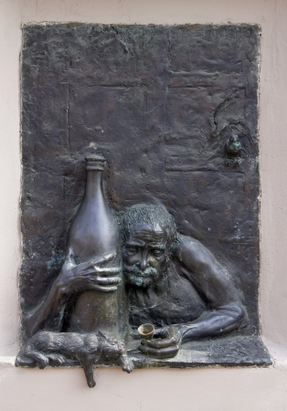 drunkard: Old  drunkard  alcoholic and a cat bronze bas-relief Stock Photo