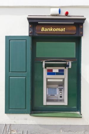 dispense: La calle dinero ATM dispensaci�n de efectivo dispositivo de producci�n de masa verde se establece en una ventana de la casa de apartamentos