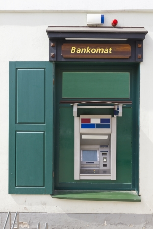 dispense: The green street money ATM cash dispense mass production  device  is established in a window of the apartment house
