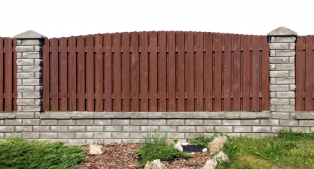 Ideal rural fence fragment  made from wooden brown  planks and gray bricks. Isolated Standard-Bild