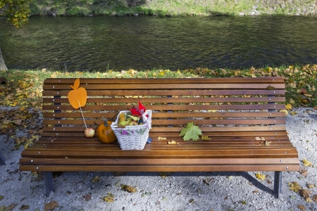 City park and the river real nature landscape, on a wooden bench is pumpkin, apples and a basket with toys. Halloween concept photo