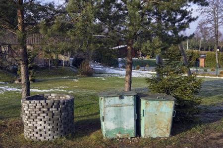 botes de basura: Latas de ladrillo y basura esta�o r�stico europeos est�n bajo los pinos. D�a soleado Foto de archivo
