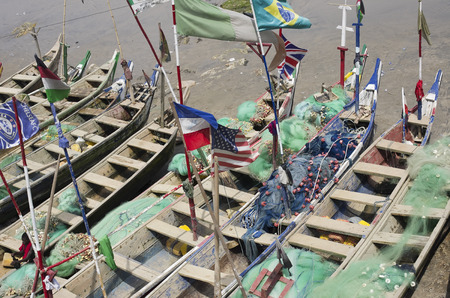 declare: ACCARA GHANA  FEBRUARY 2014: Fishing boats and flags of the USA and other countries in Ghana in February 22 2014. In 1957 Ghana became the first African nation to declare independence from European colonization.