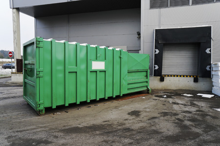 utilized: The green metal container for the utilized household appliances and electronics near shopping center. Cloudy winter day