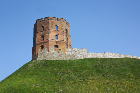 xv century: The destroyed stone tower of the XV century on the hill with spring dandelions landscape