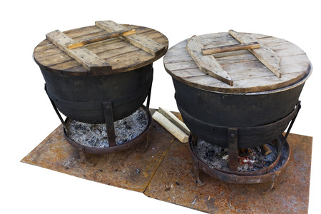 coppers: Huge pig-iron street coppers in which on the burning firewood the real pilaf cooks. Isolated with patch Stock Photo