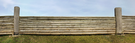 picket green: The panoramic image of very long rural fence against the sky made of the pared-down pine trunks