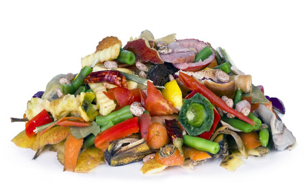 desechos organicos: El montón del comestible en descomposición orgánica de un cubo de basura se encuentra sobre una mesa blanca
