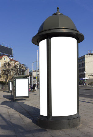 advertizing: High curbstone with billboard advertizing near a stop of public city transport. Sunny spring day. With patches isolated empty areas Stock Photo