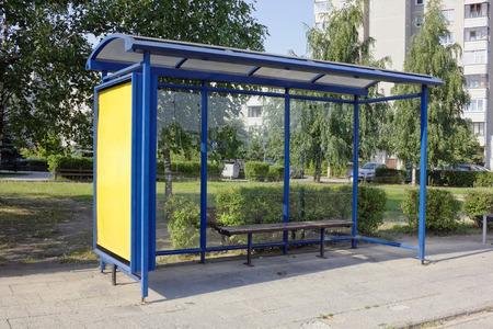 De vergeten lege massaproductie bus-stop in het slaperige zomer kleine stad. Warme zonnige dag stedelijk landschap. Stockfoto