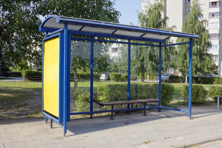 The forgotten empty mass production bus-stop in the sleepy summer small city. Hot sunny day urban landscape. Stock Photo