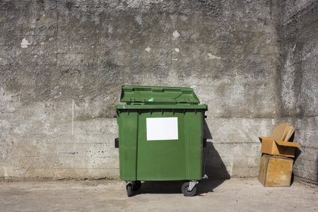 garbage bin: The lonely forgotten green trash bin in captivity of concrete walls