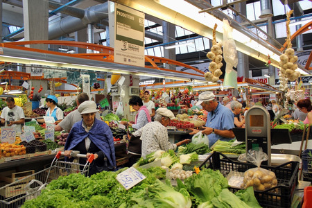 tons: MILAN, ITALY - JUNE 24, 2015: Indoor city market of fresh Italian vegetables and fruits. Italy the largest producer in Europe a citrus - over 3,3 million tons per year, and tomatoes over 5,5 million tons.