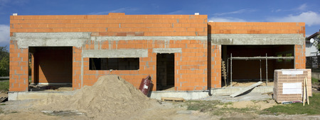 no name: Began construction of the red brick no name mass production rural shed. Sunny day landscape. Panoramic image from several shots