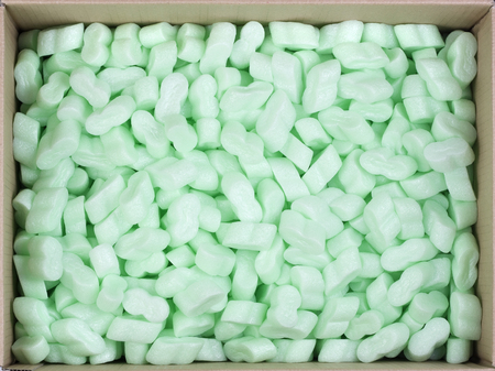 foam safe: Thebig cardboard box is filled with green bubbly plastic protective granules. Safe packing concept. Top view