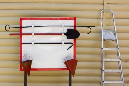firealarm: Fire board with red buckets, a hook, a shovel and a ladder concept. Stock Photo