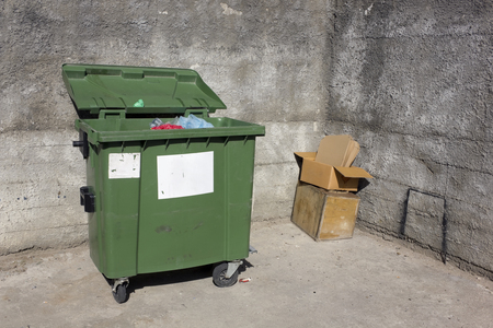 discard: Green garbage mass production container near of concrete walls