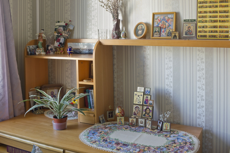 believing: MOSCOW, RUSSIA - SEPTEMBER 16, 2015: Simple standard icons, photos of relatives and religious books in the room of the believing orthodox woman. Inscriptions in Russian - bible, prayers, My God - rescue and keep