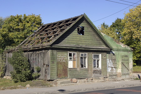 decreased: VILNIUS, LITHUANIA - OCTOBER 05, 2013: The rotten destroyed old wooden house. Europe has no money for restoration of history. Investments into restoration of houses decreased in tens times.