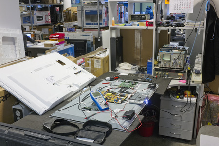 VILNIUS, LITHUANIA - DECEMBER 23, 2015:  Workplace and the equipment on repair of all brands TVs in the small service center. Repair of modern TV requires qualified personnel