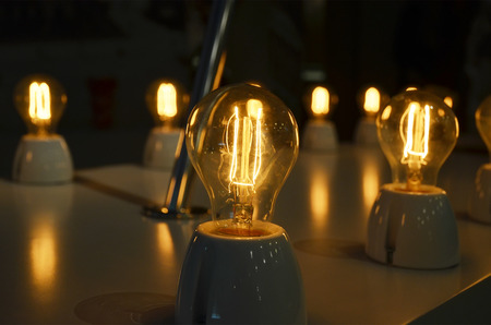 tungsten: Vintage retro bulbs shine at night. Focus on tungsten of a yellow thread of an incandescence. Gneral art soft focus