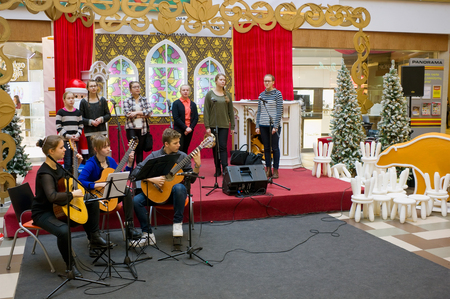 talented: VILNIUS, LITHUANIA - DECEMBER 19, 2015: Christmas traditional concert of classical music of young talented guitarists and vocalists  in Panorama  market. Each New Year concerts look thousands of people