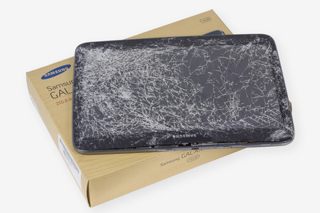 samsung galaxy: VILNIUS, LITHUANIA - DECEMBER 23, 2015:  Samsung Galaxy brand tablet with broken screen lie on table in repair service center. In 2015 Samsung sold more than 70 million phones and tablets