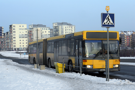 bus station: VILNIUS, LITHUANIA - JANUARY 03, 2016: The old yellow passenger city bus Mercedes at the winter  evening  frozen stop of the small European city. In 1951 Mercedes-Benz unveiled its first bus specifically designed for bus operation Editorial