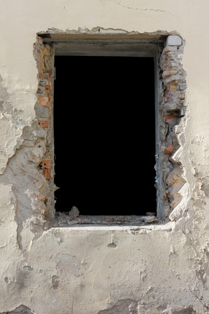 without window: Black window without glass in the old  yellow destroyed brick house