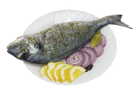 strewed: The fresh  sea grouper fish ( Dolphin, Dorado ) on a white ceramic plate with wavy edges. Fish is prepared for roasting -  is watered with a lemon, salted, strewed with pepper and spicy herbs. Isolated with patch