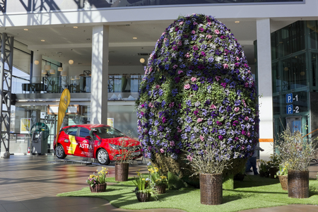 oper: VILNIUS, LITHUANIA - APRIL 02, 2016: The huge Easter egg is made of fresh spring flowers. Installation in the hall of the large shopping center Panorama. Operl Astra as gift on background