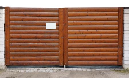 """Gate van de horizontale gelakte bruine logs. Er is een lege banner op waarin het mogelijk is om te schrijven - """"Bezit"""". gedeeltelijk geïsoleerd"""