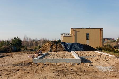 suelo arenoso: Vilnius, Lituania - FEBRERO 07, 2016: Construcci�n de amarillo casas de estilo r�stico en el �rea de suelo arenoso. Cada a�o en Lituania construir miles de casas rurales Foto de archivo