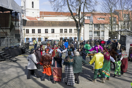 winter dance: VILNIUS, LITHUANIA - MARCH 13, 2016: The holiday and fair devoted to spring and a farewell to winter. People dance on solar streets and eat pancakes. Ahead the Lent before Easter