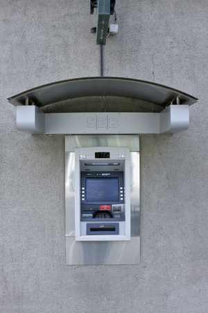 automatic transaction machine: VILNIUS, LITHUANIA - MARCH 27, 2016: The street ATM of production of Diebold brand is built in a wall of SEB bank. Diebold and IBM created a general partnership called InterBold in 1991 Editorial